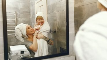Family in a bathroom. Beautiful mother with little son. Little boy brush his teeth.