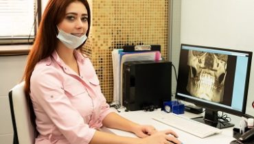 A female dentist doctor is sitting at a table, on a computer a CT scan of the jaw. The doctor is dressed in professional clothes